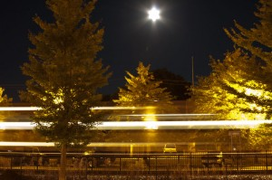 Harvest moon in village of Pawling with streaking train speeding by